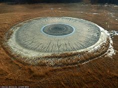 An eye for an eye: Photographer Mikhail Mikhailov was startled to see what looked like a human eye staring up at him as he flew overthe Pugachevskiy mud volcano inEast Russia