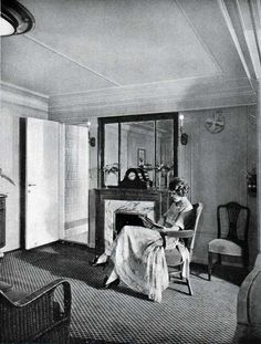 A woman (First Class Passenger) enjoys a quiet moment reading in the Sitting Room of her suite on the S.S. Leviathan of the United States Lines circa 1923. Blue hangings and blue coverings on the satin wood furniture are charming against corn colored walls.