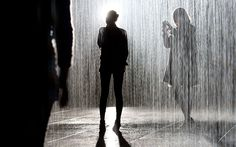 Visitors walk through an art installation entitled 'Rain Room' during a photocall at the Barbican in London, on October 3, 2012. The 'Rain R...
