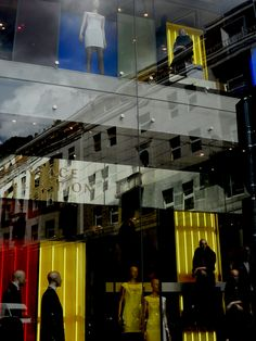 Un edificio riflesso nelle vetrine della maison Versace. Milano