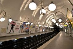 """""""We are standing on a black asphalt platform. Above our heads the white tile ceiling is reassuringly high, and white pendant lights the size of beach balls glow like harvest moons. But at each end of the asphalt platform black D-shaped holes gape like hungry mouths. Riding the Metro means entering one of those mouths."""" (from THE PARIS EFFECT)"""