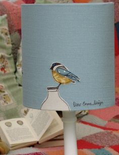 The second design is a very limited edition of hand embroidered blue tit applique lampshades. Each of the 3 birds atop the milk bottles are individually sewn from a multitude of fabric scraps onto a beautiful quality linen before being laminated to a f. Free Motion Embroidery, Free Machine Embroidery, Embroidery Applique, Luminaria Diy, Sewing Crafts, Sewing Projects, Home And Deco, Lamp Shades, Fabric Art