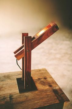 This desk lamp is handmade from black walnut joined together by a cross joint and a steel base that brings out the natural tones of the wood while keeping it raw and organic.