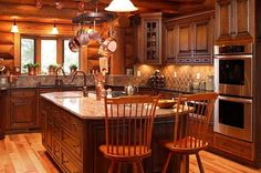 Though packed with modern amenities, this log cabin kitchen uses a palette of woodsy colors and finishes made of stone, wood and metal to create a rustic aesthetic. Copper pots hanging from a pot rack light fixture and copper planters complete the decor. Paul Bradham