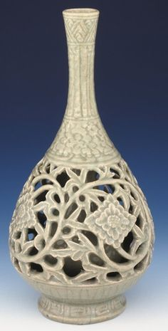 Porcelain pear-shaped double vase with openwork and green glaze. This pear-shaped double vase has a tall narrow flared neck and raised foot ring; the base is partially glazed, the foot ring and inside are fully glazed with a crackled glassy broad-bean-coloured glaze. The exterior of the vase is incised with a key-fret border around the thickly potted everted foot. 340mm tall, c.1522-1620, Ming dynasty,  ...cont'd