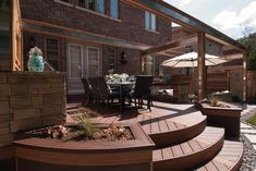 """This deck's main dining and lounge zones are connected with steel-accented aerial beams and a two-way outdoor fireplace.  The dining area transitions down to the yard with curved stairs and built-in planter boxes.  From """"Decked Out"""" project """"The BBQ Deck"""". Deck design by Paul Lafrance Design."""