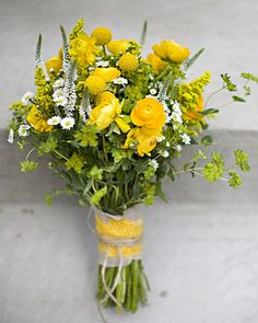 Wild flowers and herbs in a sunny clutch of ranunculus and craspedia