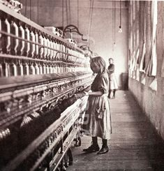 Children and overseer at work in the spinning shed of an American cotton mill, 1910..