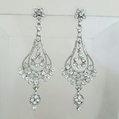 Formal statement chandelier earrings silver bling Silver-tone earrings with clear rhinestones.  Worn once for a formal.  All of the rhinestones are intact - nothing missing.  I got them at a Jessica McClintock store and don't know what the metal is composed of. Jessica McClintock Jewelry Earrings