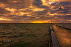Pier to the Light - Sun shining behind a very cloudy day along a pier in Victoria,Australia,