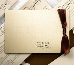 Elegant Shimmer Pocket Wedding Invitation. An elegant cocoa satin ribbon secures the jacket of this fold over design in shimmering Champagne with Sable text. A delicate calligraph swirl embellishes the couple's initials and wedding date.