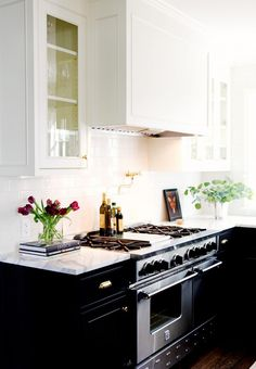 Classic kitchen with white upper cabinets and black lower cabinets, marble countertops, and a white subway tile backsplash.