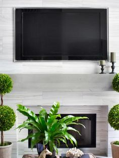 Due to careful planning, design considerations and ample safety measures, a flat-panel TV above this great room's modern mantel is functional and aesthetically pleasing.