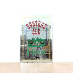This Hunter's Ale drought mirror is featured in a shiny nickel and glass. This fun, frameless accent mirror has 'Hunter's Ale' emblazoned across the top, an illustration in the middle, and painted yellow borders. Perfect kitschy piece for a home bar! #americantraditional #decor #mirror #sandiegovintage #vintagefurniture