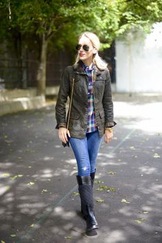 Katie's Bliss wearing a Barbour womens waxed utility jacket, plaid shirt, Tory Burch riding boots and Saint Laurent wallet on a chain.