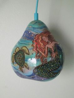 Mystical and real creatures of the ocean is the theme of this unique gourd lamp. This piece is an original painting as well as a lamp. A large, pear-shaped gourd was selected for this lamp, and was drilled with a design of a beautiful mermaid and three sea turtles amongst the tropical ocean currents. This scene was painted onto the surface of the gourd to look good even when the light is off, and a variety of beads in tones of green and teal were incorporated into the mermaids tail to add…
