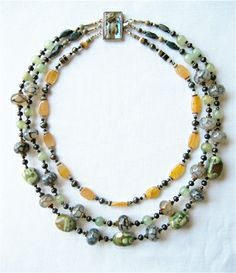 A simple three-strand necklace composed of polished stones from the earth and pearls and abalone shells from the sea. An elegant, understated piece in subtle shades of grey and greens set off by a strand of tangerine orange stones. The closure in a square abalone box clasp. The strands measure approximately 16, 18 and 20 inches.