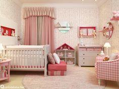 Enxoval de bebê rosa com detalhes em listras e xadrez. A casa de boneca também decora o ambiente.