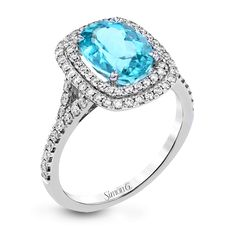 This lovely vintage-inspired 18k white gold double halo ring has a 2.48 ct paraiba tourmaline center stone and is set with .55 ctw of white diamonds.