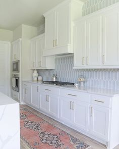 White kitchen cabinets pair with brass pulls and white quartz countertops in a transitional design space accessorized with blue glass picket backsplash tiles and a pink runner. White Shaker Kitchen Cabinets, Backsplash For White Cabinets, Shaker Style Cabinets, Blue Kitchen Backsplash, Backsplash Tile, Kitchen Cabinets With Handles, Kitchen Cabinetry, Backsplashes With White Cabinets, Kitchen Cabinets European Style