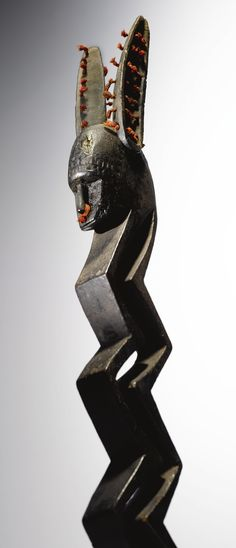 Bamana Zigzag Figure, Mali H 67.2 cm  This magnificent Bamana sculpture, previously in the collections of two of the great connoisseurs of African art of the twentieth century, Charles Ratton and William Rubin, displays an extremely rare zoo-anthropomorphic iconography, combining an elongated multi-segmented zigzag body in vertical orientation with a humanoid head and two long zoomorphic ears. Only two comparable sculptures are known...