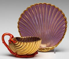 A.P.L. Dagoty~Porcelain~Gilded~Shell-formed~cup and saucer in purple~The cup with coral shaped handle and base~Painted floral in the interior~Origin France~Circa 1801-1810