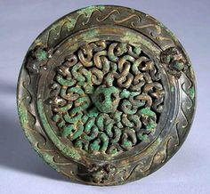 Bronze mirror of the Warring States Period.  The Bronze Mirrors of the Warring States Period are mainly round ones, decorated by double layer lines of mountains, animals, flowers and leave.