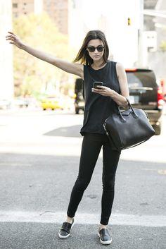Comprar ropa de este look: https://lookastic.es/moda-mujer/looks/camiseta-sin-manga-vaqueros-pitillo-zapatillas-slip-on-bolsa-tote-gafas-de-sol/3505 — Gafas de Sol Negras — Camiseta sin Manga Negra — Bolsa Tote de Cuero Negra — Vaqueros Pitillo Negros — Zapatillas Slip-on de Cuero Negras