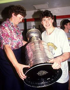 Jaromir Jagr holding the Stanley Cup with his mom in the dressing room , 1991