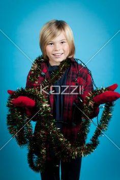 smiling boy holding christmas decorations. - Smiling boy holding christmas decorations over turquoise background, Model: Josh Chapman
