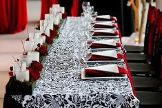 Black and white damask bridal table with red roses and candles wedding reception