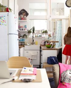 Open view of Éléonore's kitchen space and view into bathroom.  IKEA small-space inspiration kitchen: floating corner shelves, hanging herb garden and handing dishwashing accessories, double decker counter, extended with a stool.