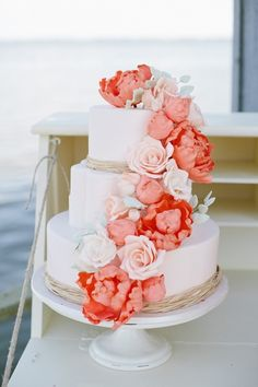 I love this. Coral flowers with light blue ribbons on the bottom of each tier. Perfect.