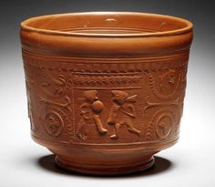 A Roman red gloss ware bowl with gladiator decoration Circa 1st Century A.D. The deep terra sigillata bowl with moulded decoration including four panels of gladiators in combat interspersed with lions, bears and birds, 5½in (13.5cm) high, 6¼in (15.5cm) diam
