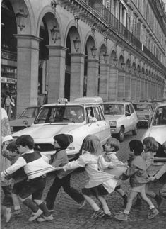 black and white photo of children crossing the street