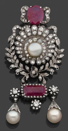An antique platinum, gold, ruby, pearl, and diamond brooch.