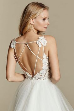 Ivory lace and tulle bridal ball gown, scalloped V-neck bodice with low open back and strap detail, tiered tulle skirt with horsehair trim. Back View