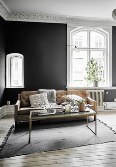 Black walls really make the furniture stand out - this simple monochrome colour palette is set off to perfection with the black wall behind it.