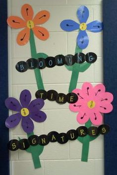 """blooming time signatures"" bulletin board display. (center of flower has time signature, number of petals represent beats/measure, note written on petal represents what note gets the beat.)"