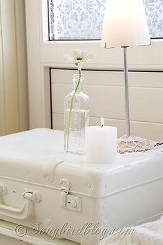 white suitcase bedside table