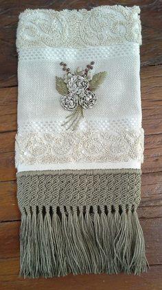 Toalha de lavabo com aplicação de flores de sianinha, bordada <br>à mão com acabamento em macramé.