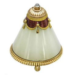 A BELLE EPOQUE GOLD, ENAMEL AND HARDSTONE BELL-PUSH, BY FABERGÉ   The bowenite pyramid on ridged gold base and three feet, to the red guilloché enamel and bi-coloured gold fringed cap with cabochon moonstone push-piece, circa 1900, 6.5 cm high, in fitted Fabergé wooden case  Signed Fabergé (Cyrillic), indistinct workmaster's mark, with inventory no. 56838