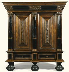 A Dutch carved rosewood, ebony and walnut  'rankenkast', second half 17th century with an overhanging cornice with a lion mask and seraphim at the angles, with a central panel carved with a bird amongst foliage, above two panelled doors with ribbon-tied floral trails flanked by demi-columns opening to reveal a long narrow drawer and a shelf, the sides with raised panels as the doors, on bun feet Sotheby's
