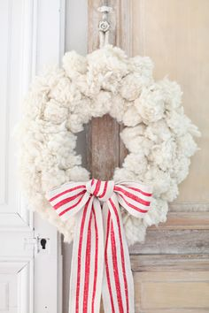 Pompom Wreath Create a wreath using thick pompoms like this one from Anthropoligie. Adorn it with a simple bow and voila!