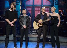 """25 years ago in 1989 (and before his castmates were born) Woody Harrelson hosted """"Saturday Night Live"""" for the first time. To honor that anniversary, the actor grabbed a guitar and sang a tune from Taylor Swift's popular album, 1989, joined by """"Hunger Games"""" co-stars Liam Hemsworth, Josh Hutcherson and Jennifer Lawrence."""