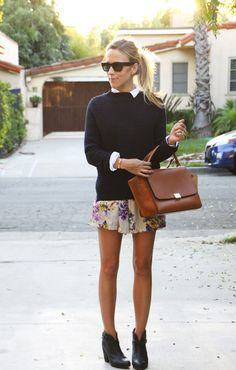 collared shirt under a chunky sweater over a skirt