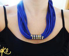 collar hecho con tela, con detalle central de alambre plano, cierre del mismo alambre, cierre con cadena dorada y detalle colgante, color violeta y dorado....