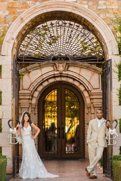 """This bride and groom posed in our beautiful gate way with their detail, """"B"""" to celebrate their new share last name! #wedding #arizona #villasiena #villasienabride #villasienawedding #b #bride #groom #door #gate #weddingpicture #idea"""