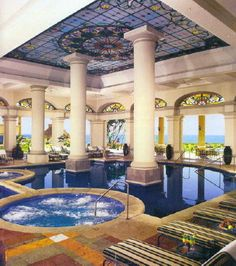 Extravagant indoor swimming pool with a view of the ocean.