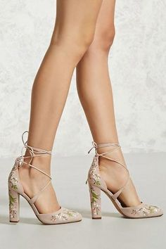 A pair of wide-fit faux suede heels featuring a pointed toe, lace-up design, floral embroidery, a chunky heel, and high-polish aglets.